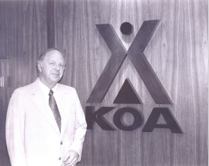 Kampgrounds of America Inc. founder Dave Drum in front of the iconic KOA logo in 1964.